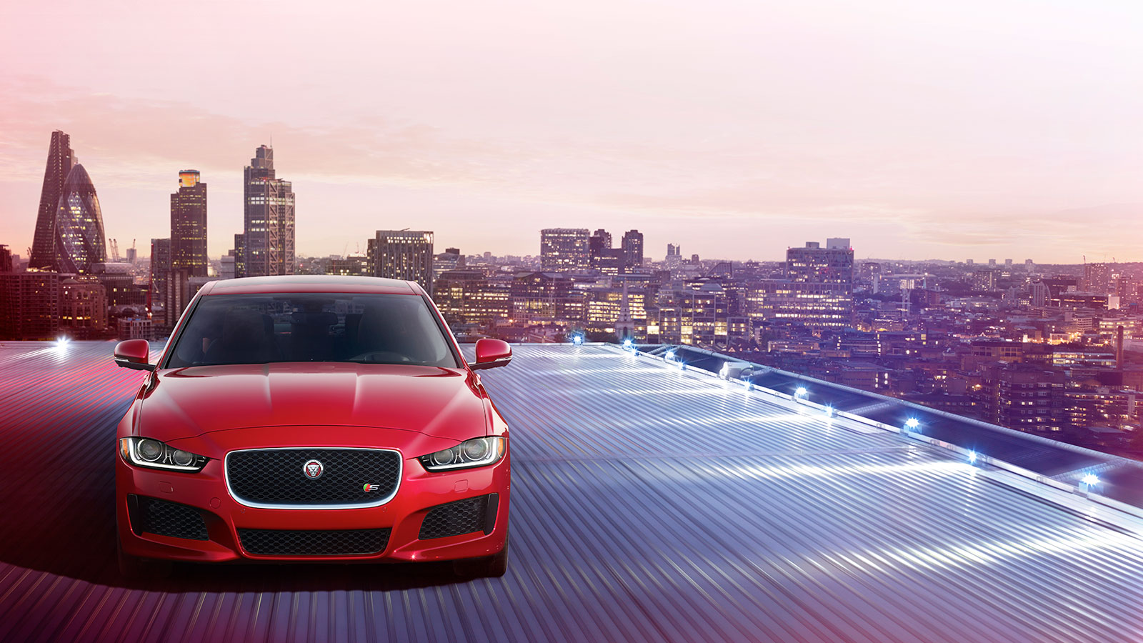 XE on a lit rooftop above a city skyline.