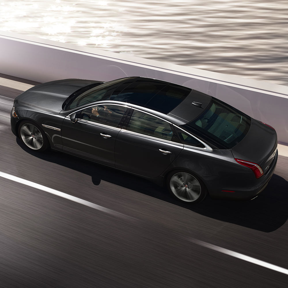 Jaguar XJ driving on road.