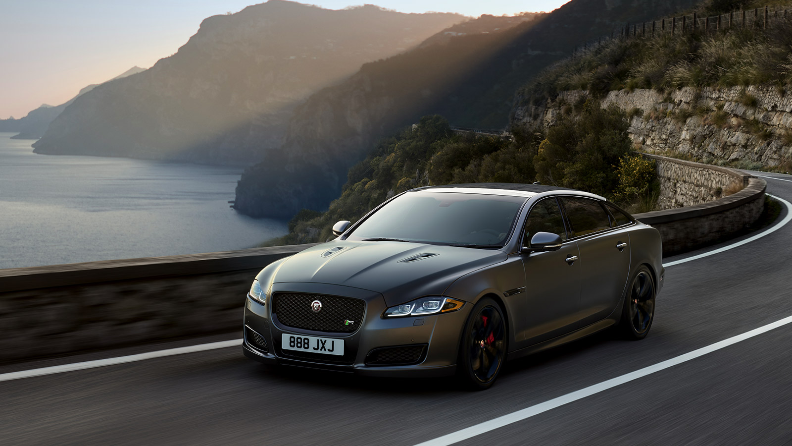 Grey Jaguar driving on-road by the sea.