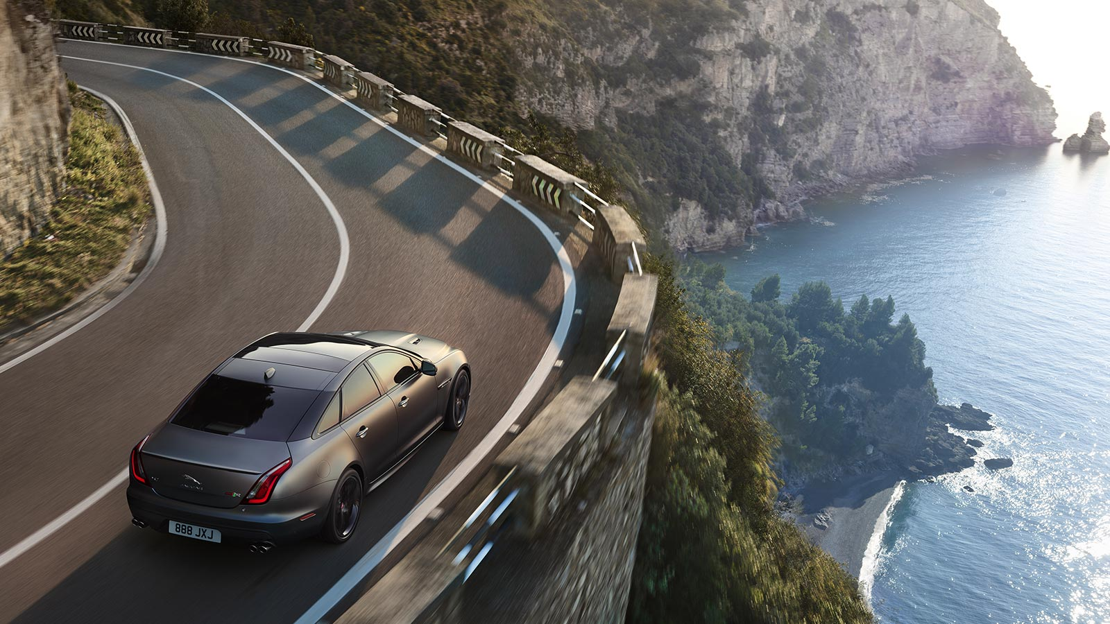 High view of jaguar driving on-road by the sea.