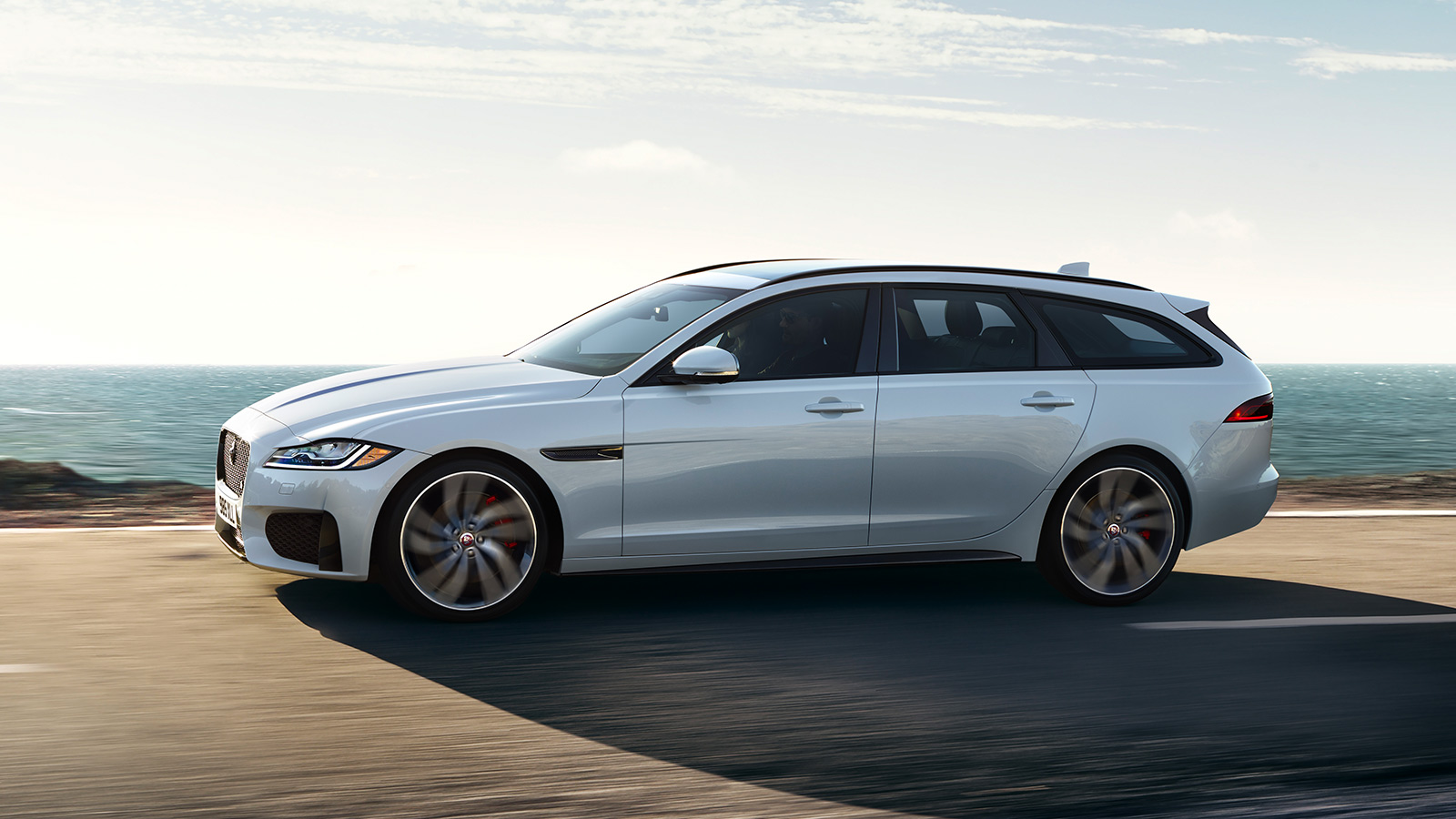 Side profile of Jaguar XF next to the sea.