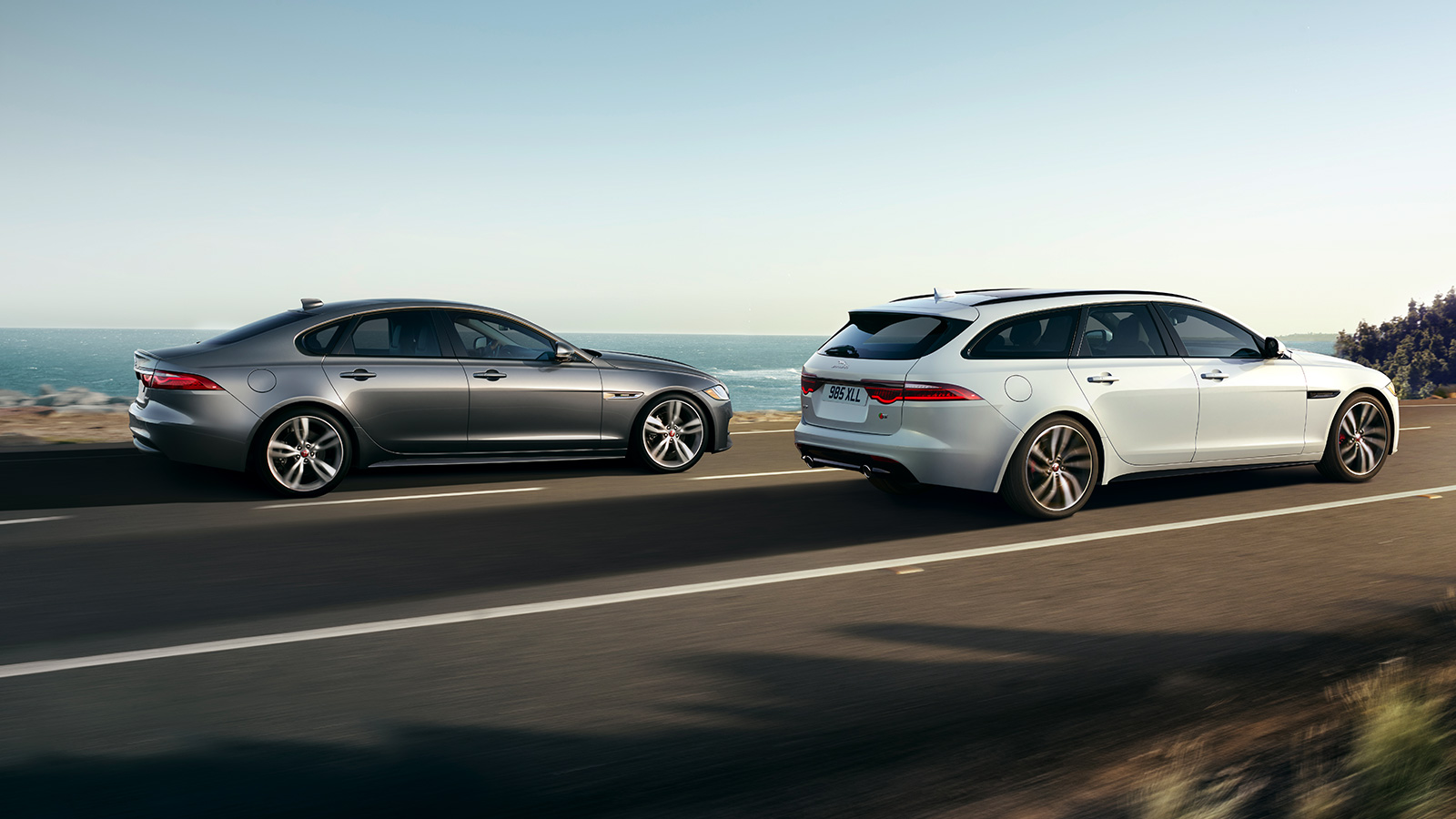 Two Jaguars driving by the sea.