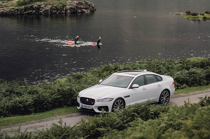 Jaguar XF drive by waterside, with kayaks in the water.
