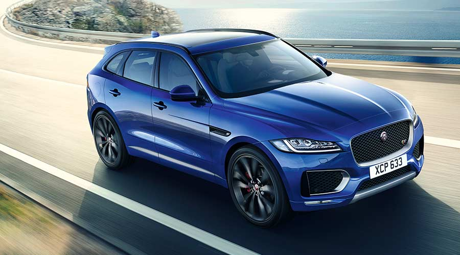 Blue F-PACE driving by lake.