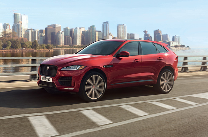 red fpace driving on a road.