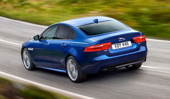 A Blue Jaguar XE Driving on a Road.