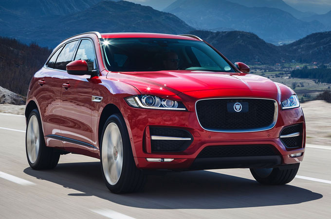 Red F-PACE driving in mountainous region.