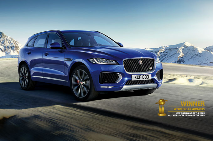 Blue F-PACE driving in mountainous region.