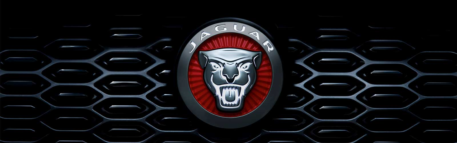Front right headlight of a red Jaguar.