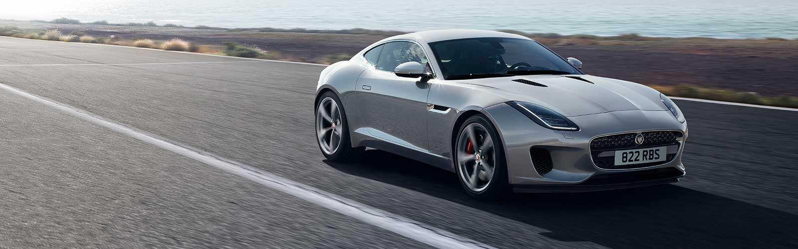 Black F-Type driving down country road.