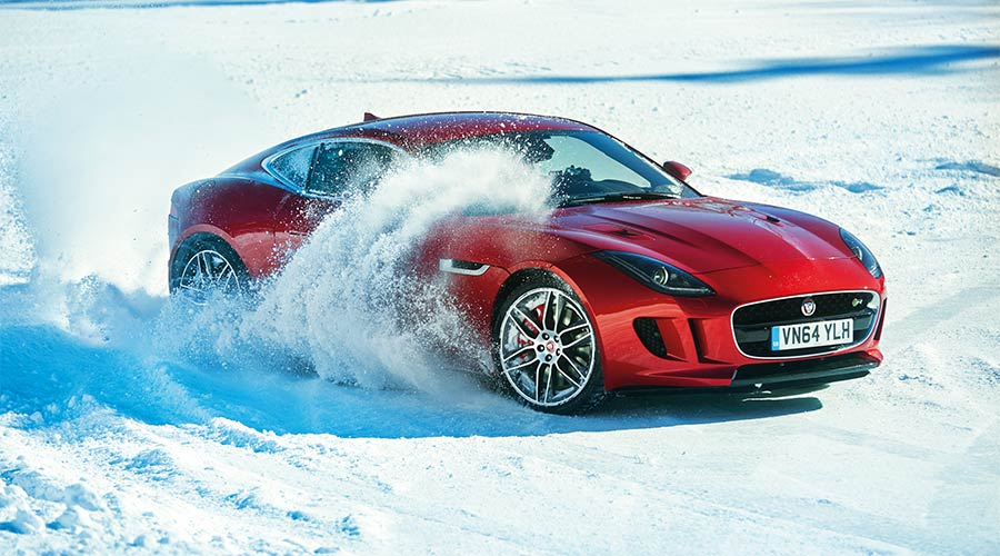 Red F-TYPE driving on snow.