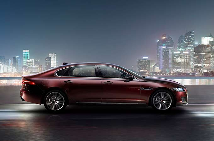 Deep red car side facing with night city scene