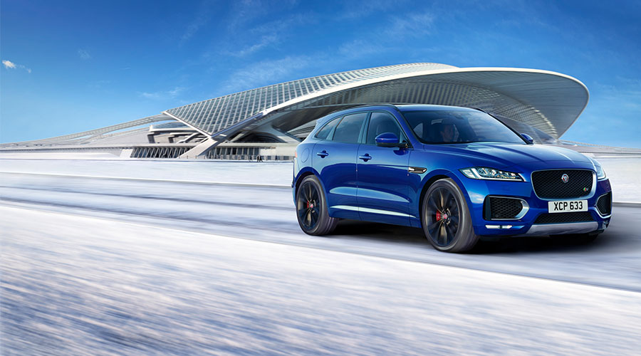 Blue F-PACE driving in snow.