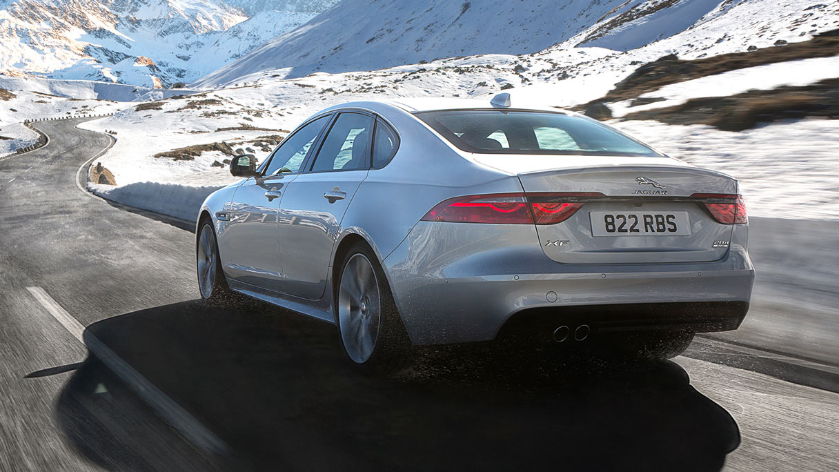 Rear view of silver XF driving through mountains.