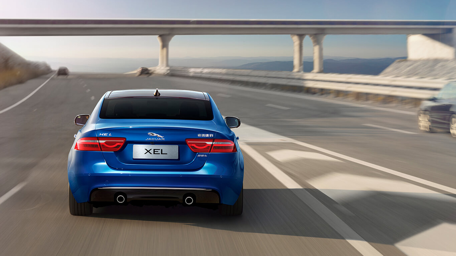 Rear view of a Blue Jaguar XEL driving on a highway.