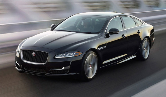 Jaguar XJ driving down a road