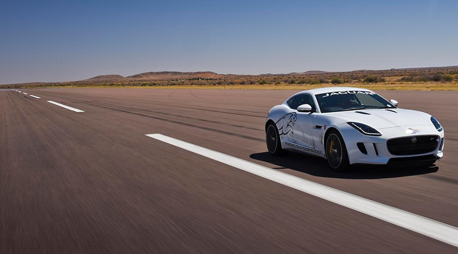 White Jaguar F-TYPE driving down a long road.