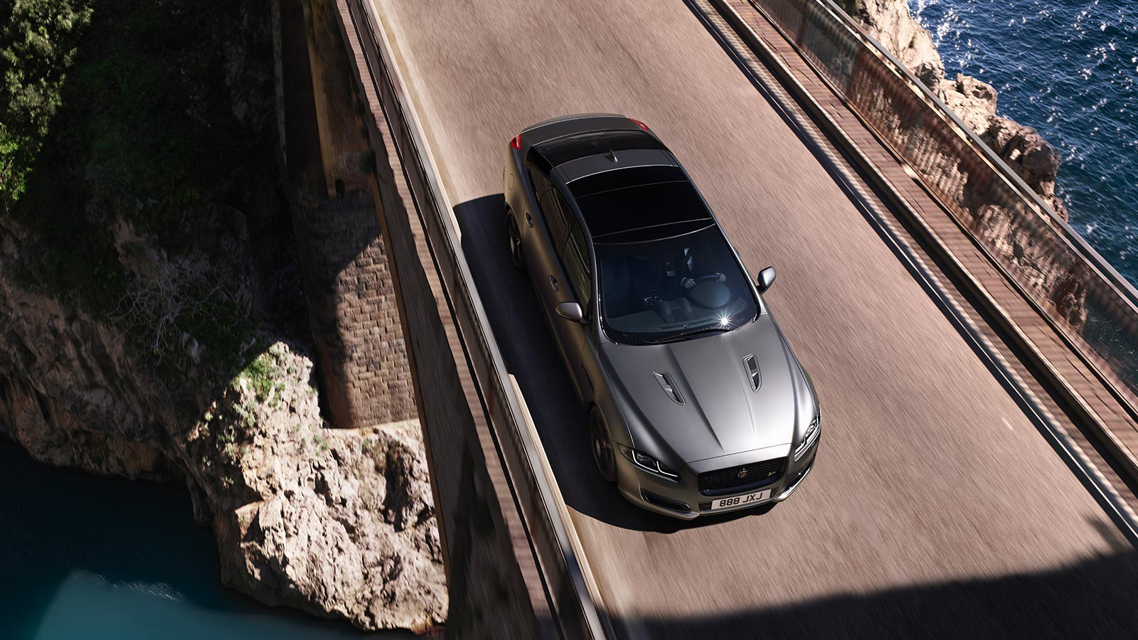 high view of XJ driving over bridge.