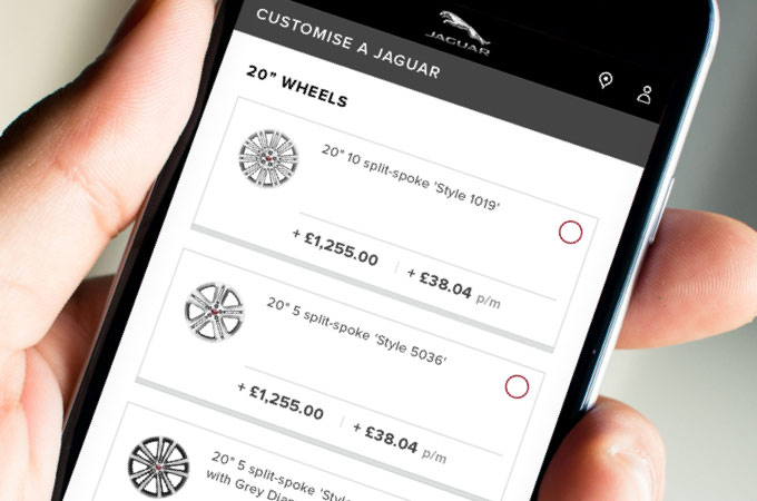 mobile phone being held looking at different wheels on the jaguar website.