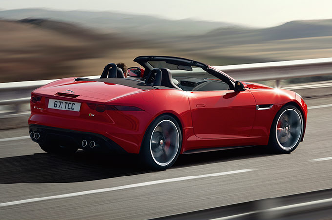 Red F-TYPE driving on highway.