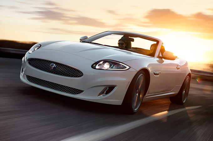 White XK driving in countryside.