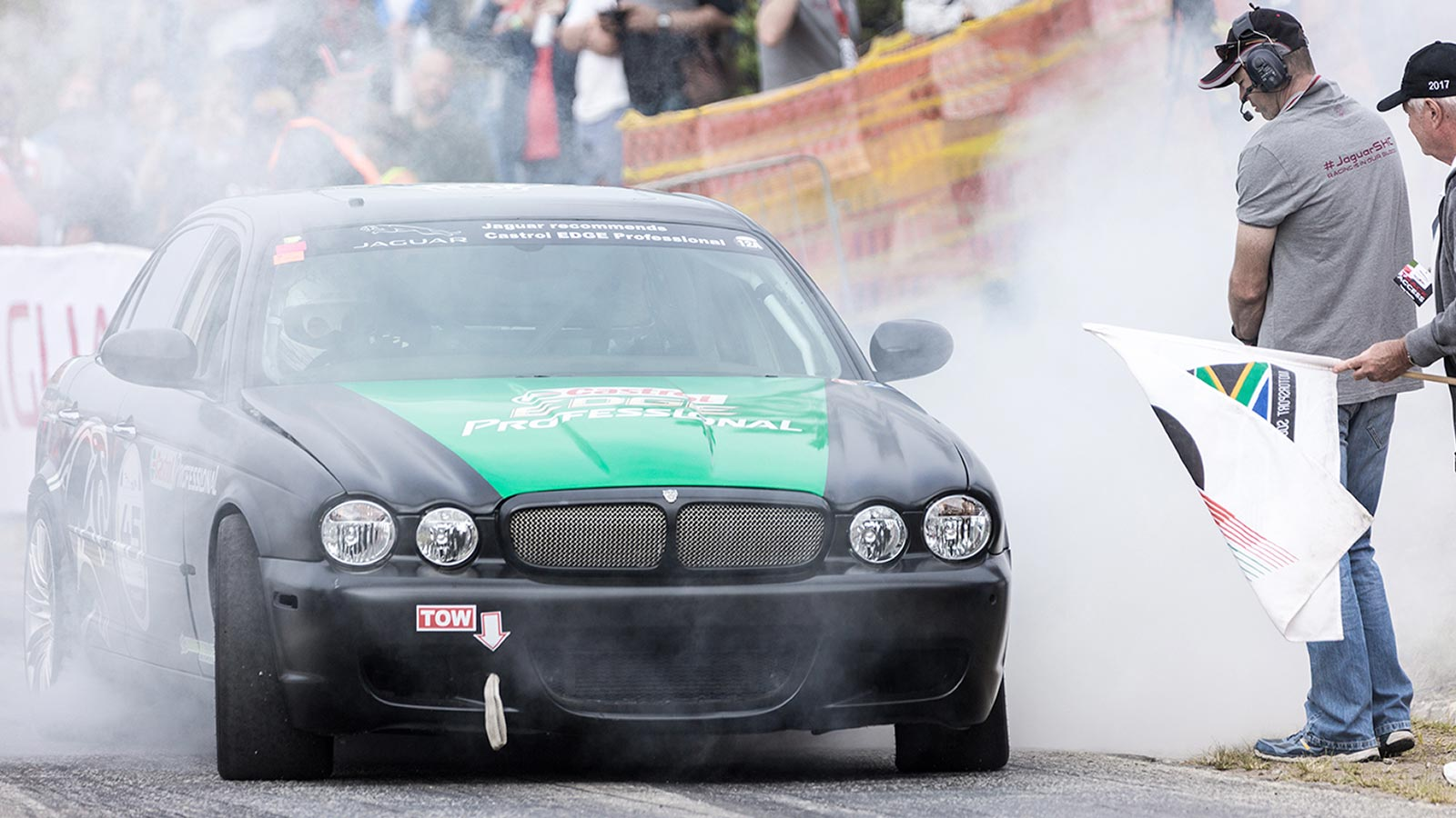 jaguar driving on a road with smoke around it.