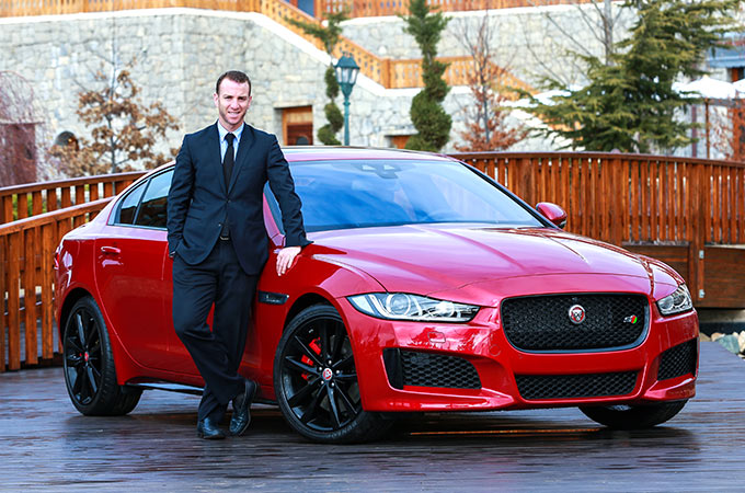 Man leaning against red Jaguar