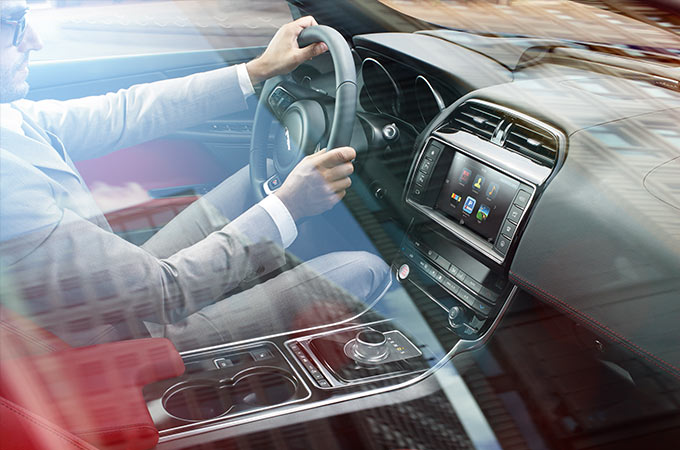 Man in a suit, driving his Jaguar, with InControl Apps on the Touchscreen