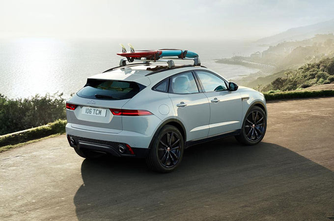 Jaguar with a surfboard on the roof.