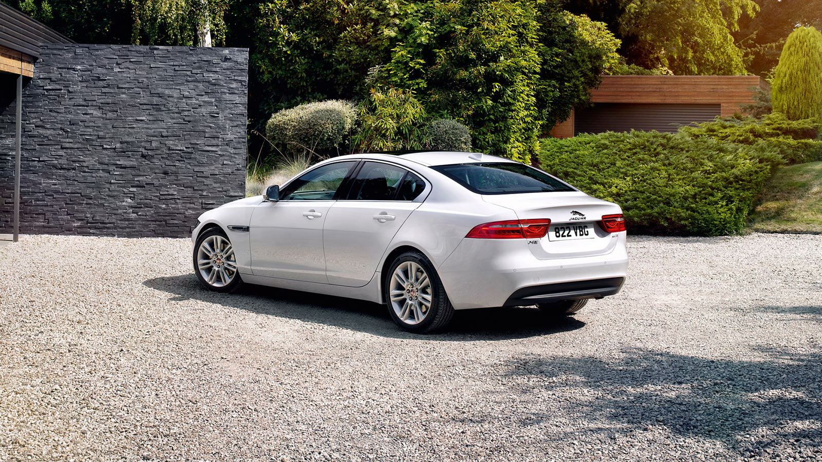 White jaguar xe parked indfront of a house.