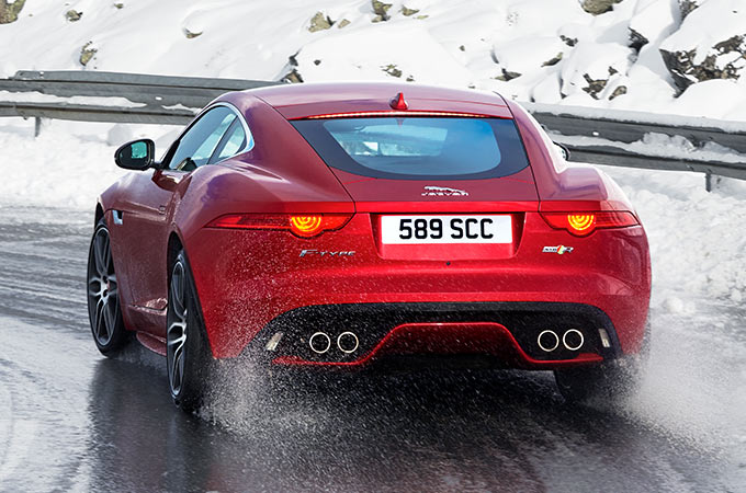 Red F-type driving on an icy road.