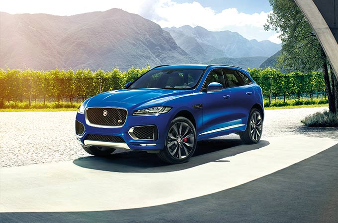 Blue F-PACE parked in front of landscape.