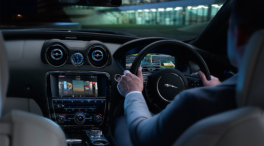 Connectivity - Interior view of man driving XE.