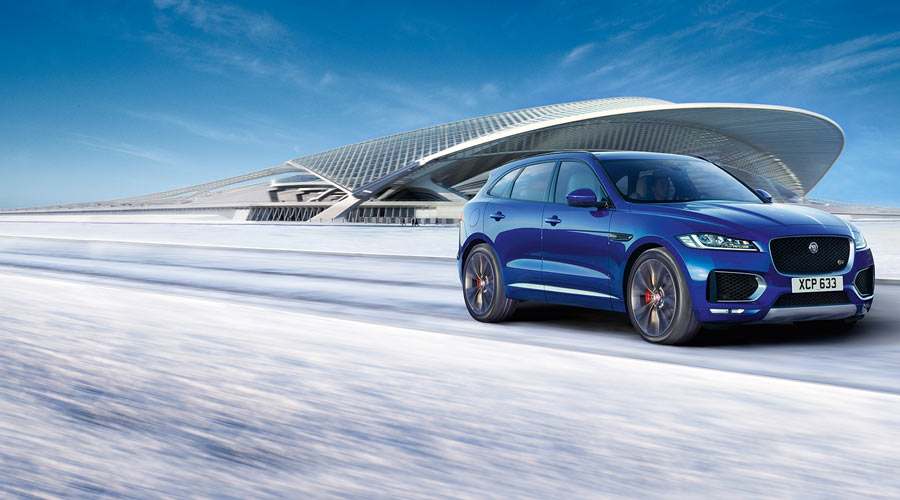 Jaguar F-Pace driving on a snowy road in front of a large modern building.