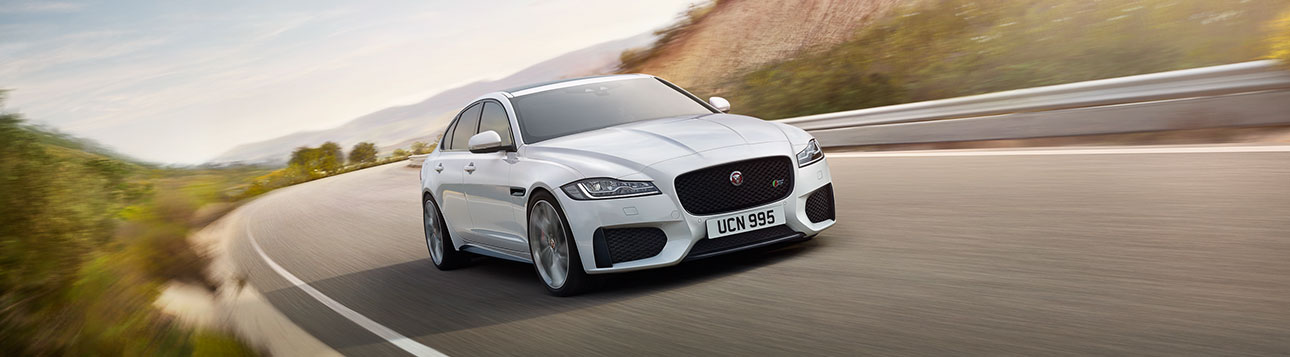 Jaguar white XF close-up while in motion.