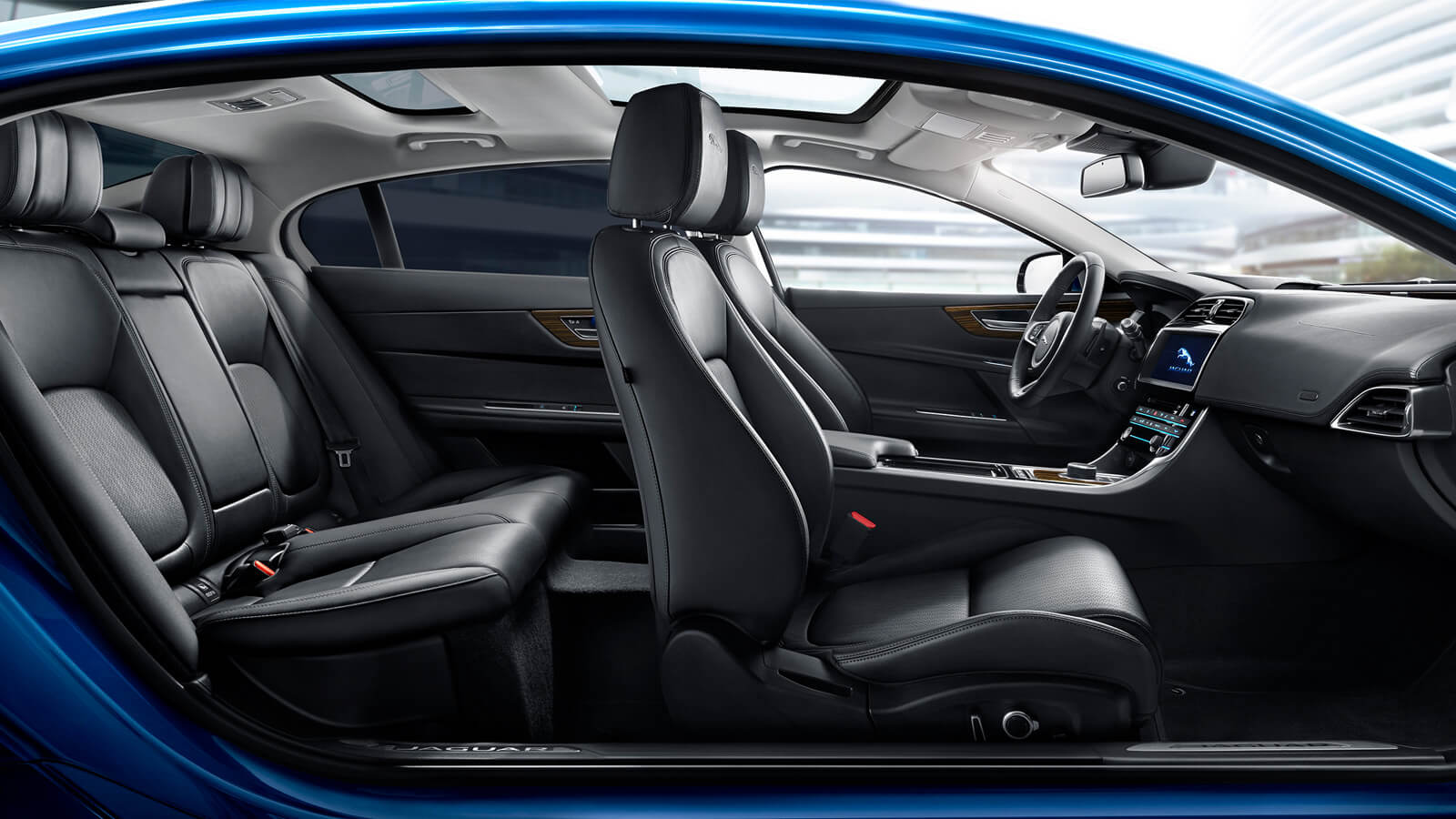 side view of the interior of a blue jaguar xe.