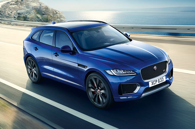 Blue F-PACE driving next to lake.