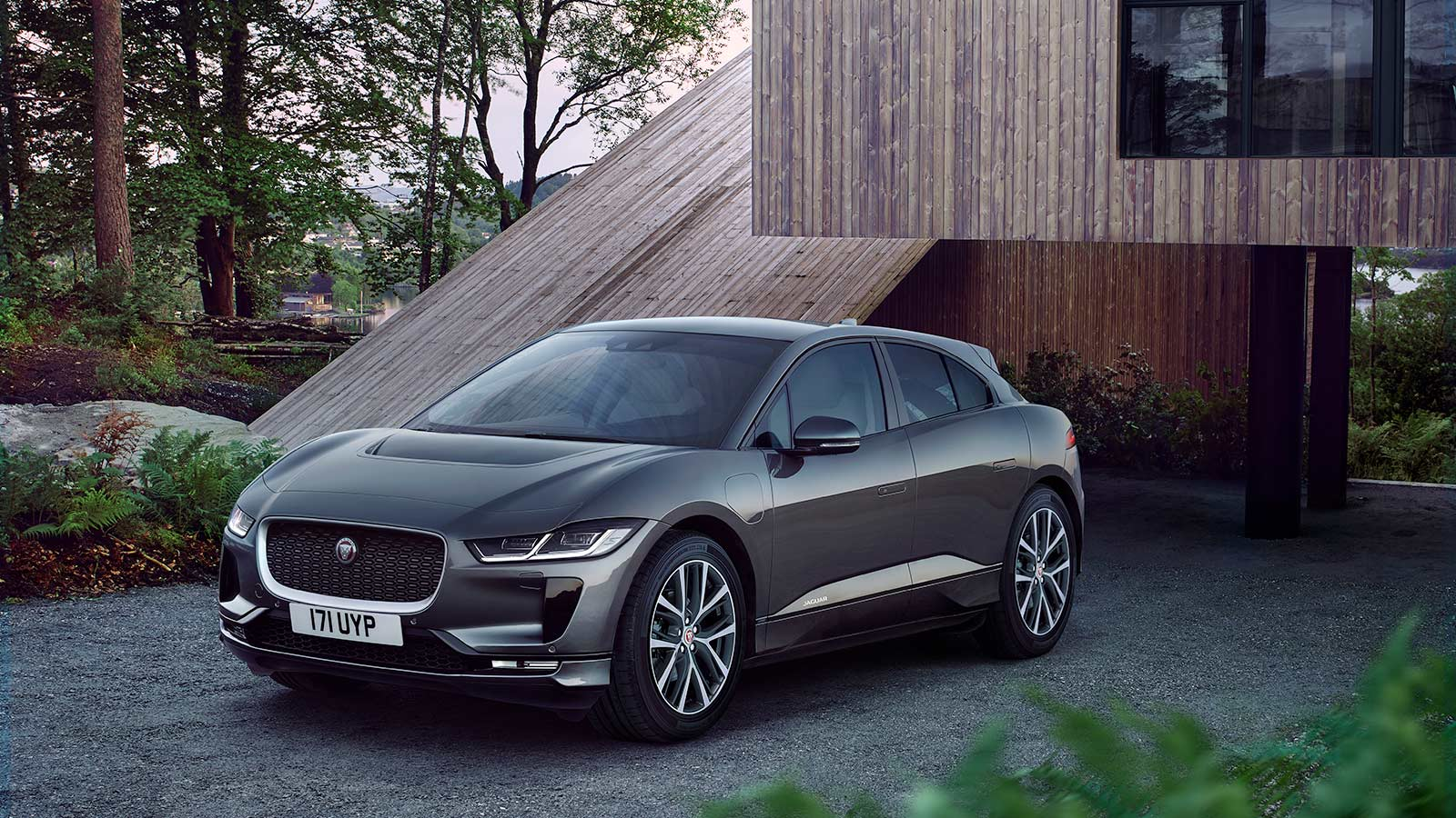 Jaguar I-PACE parked in front of a wooden suburb house.