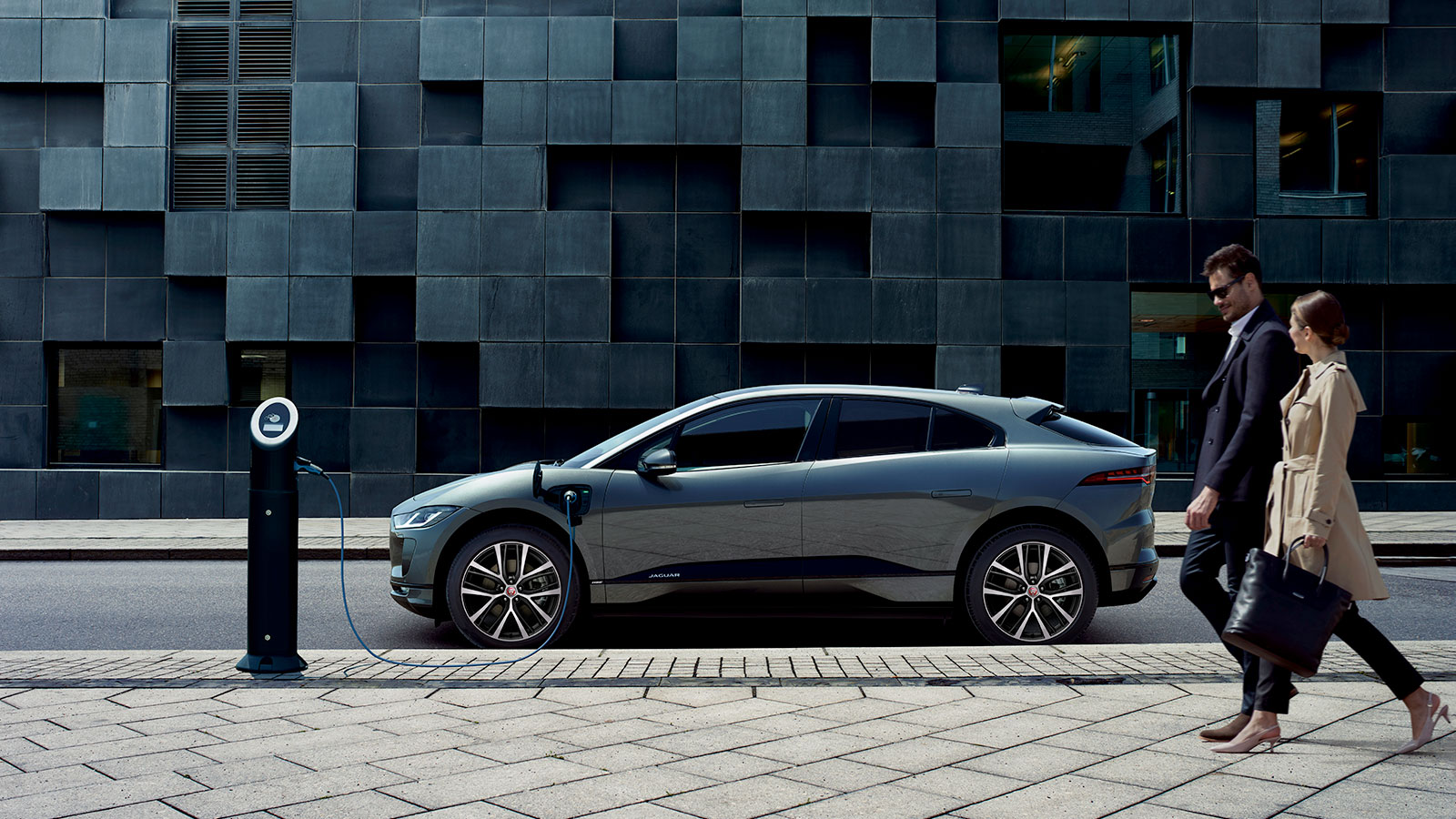 Jaguar I-PACE in a city environment, with a charging point and a couple walking by.