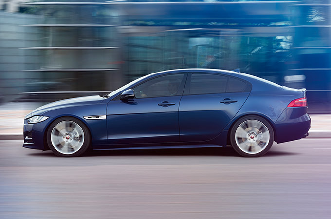 XE in front of glass building.
