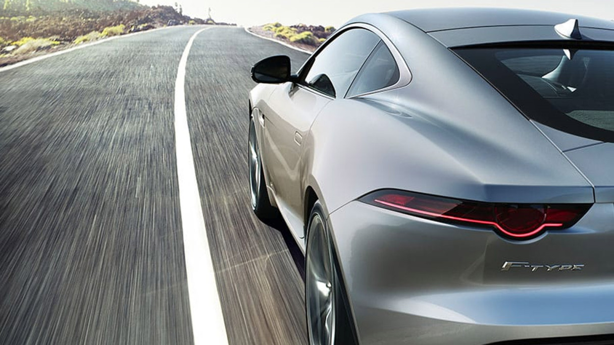 A closeup rear three quarter angle of an f-type driving along a road.