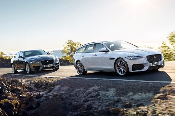 Jaguar XF and XFSB driving down a road.