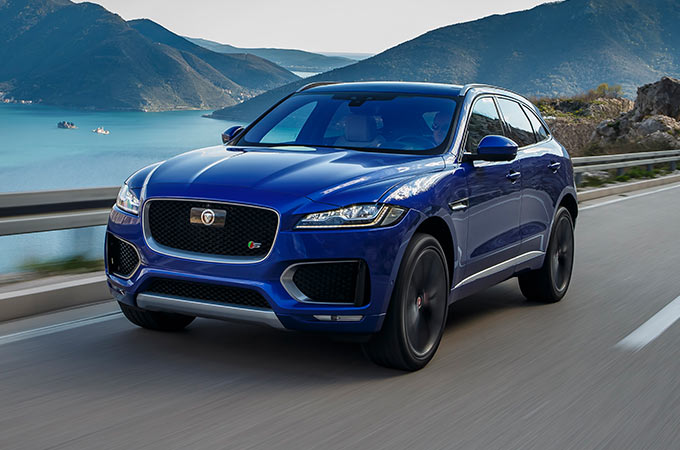 Blue Jaguar F-PACE driving along a lake.