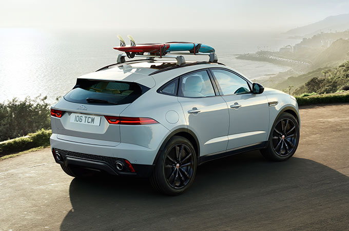 White E-PACE with surfboard attached overlooking coastline.