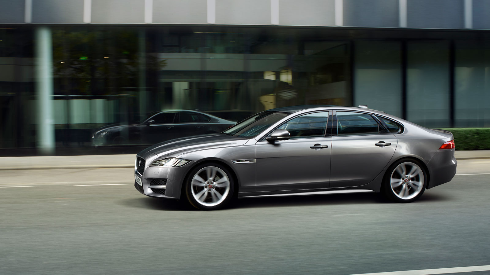 Side Profile View of Jaguar XF Driving In City.
