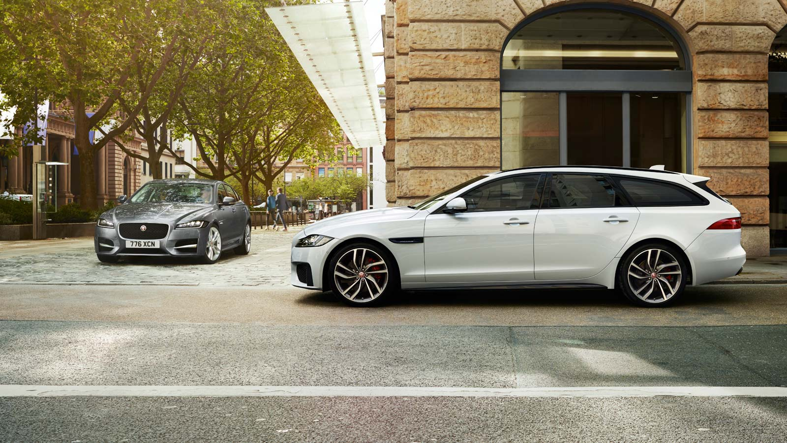 White Jaguar XF Driving By Building
