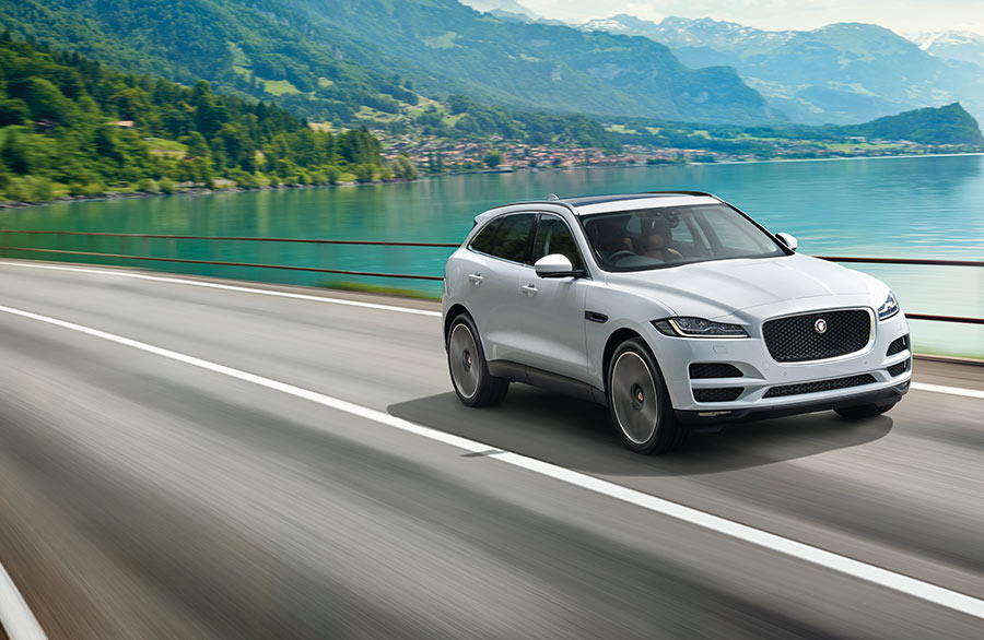 White F-Pace Driving on bridge.