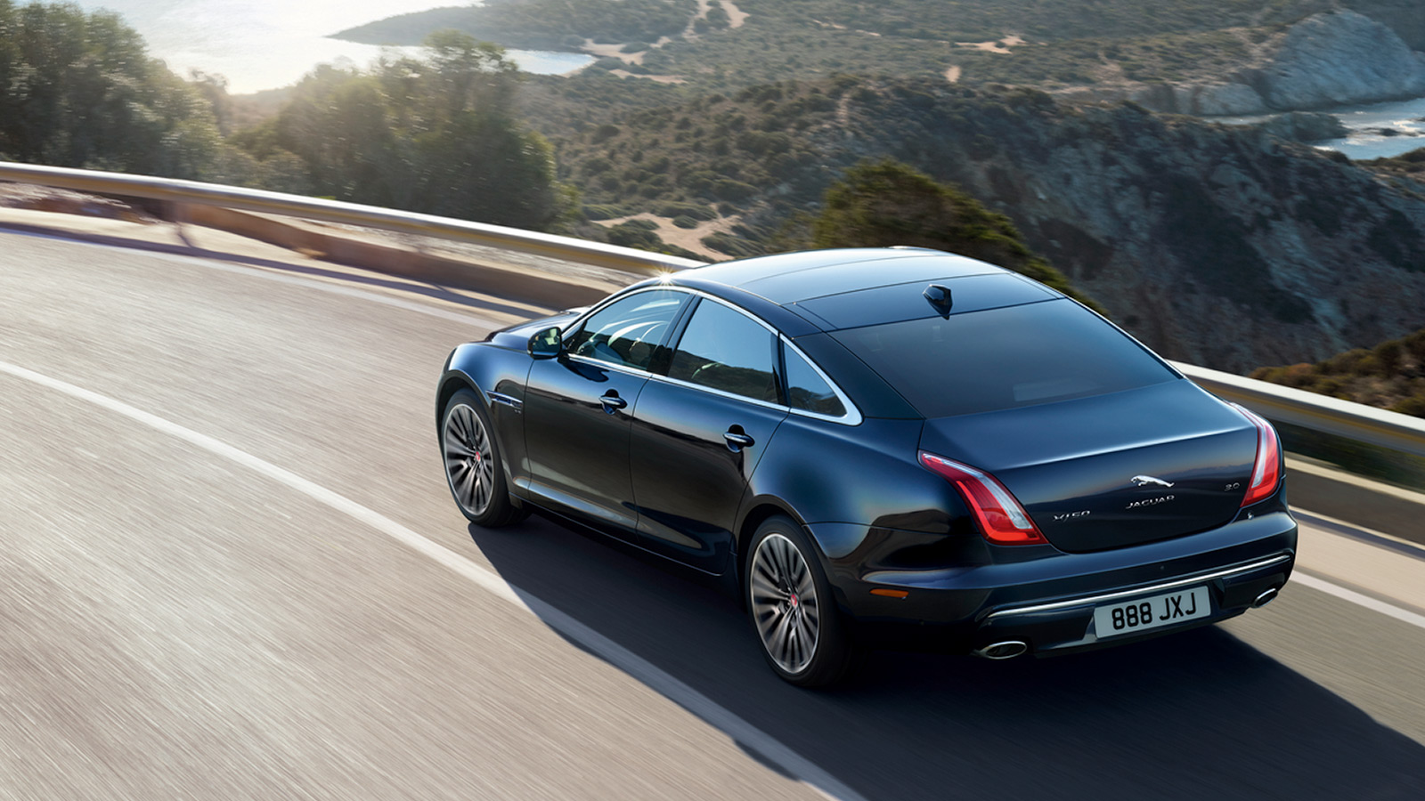 Rear view of XJ driving on road.