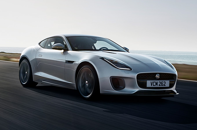 Silver Jaguar F-Type driving on road.