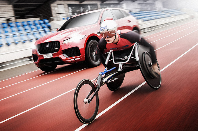 Marcel Hug riding a wheel chair with an f-pace.